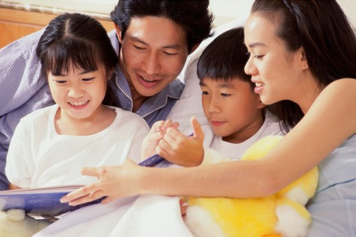 Stock Photo: 1188-847B Mid adult couple playing with their son and daughter in the bed