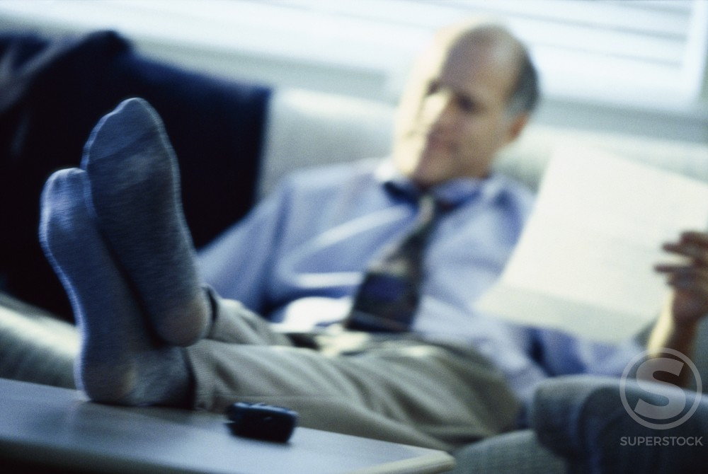 Businessman with his feet up on a desk holding a sheet of paper : Stock Photo