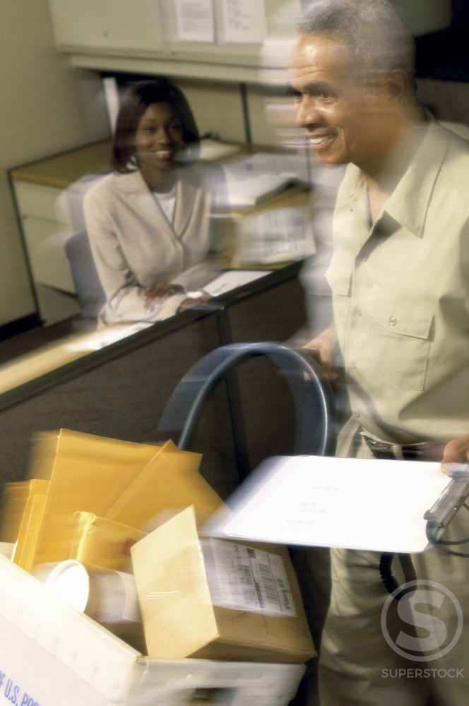 Stock Photo: 1189-1211A Mature man pushing a mail trolley in an office