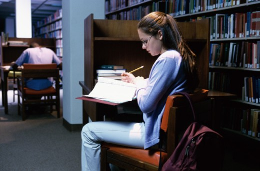 Stock Photo: 1189-1324C Side profile of a teenage girl reading a book in a library