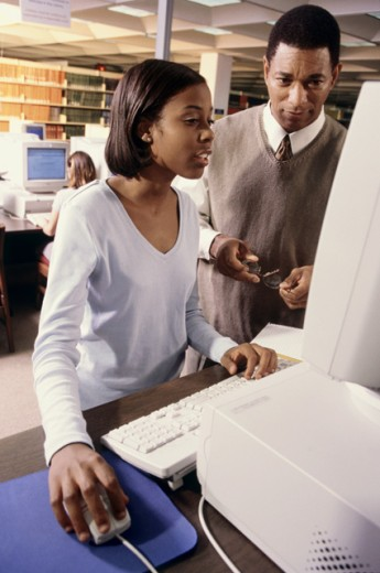 Stock Photo: 1189-1365A Male teacher and a teenage girl in front of a computer