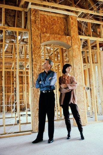 Mid adult couple standing in their incomplete house : Stock Photo