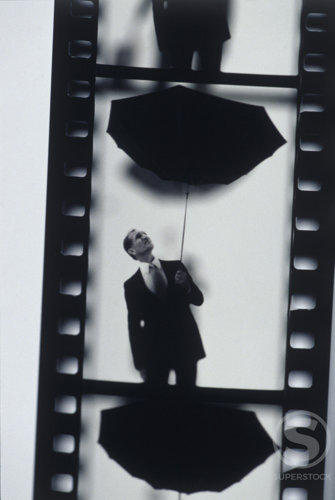 Close-up of a film strip of a businessman holding an umbrella up side down : Stock Photo