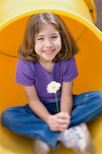Girl sitting in a pipe and holding a daisy : Stock Photo