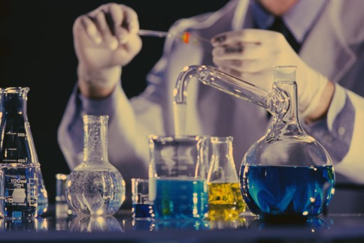 Stock Photo: 1189-1697 Mid section view of a scientist holding a test tube in a laboratory