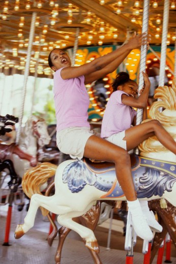 Stock Photo: 1189-1843C Mid adult woman with her daughter riding a carousel horse