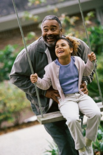 Stock Photo: 1189-2204A Grandfather pushing his granddaughter on a swing