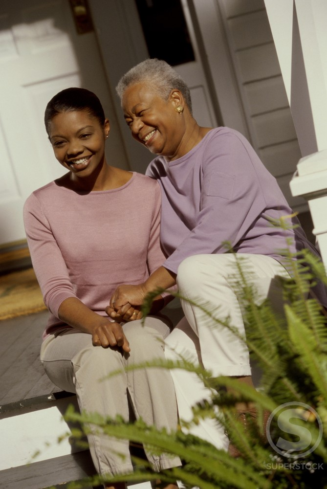 Daughter sitting with her mother on a porch : Stock Photo