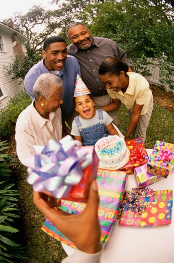 High angle view of a girl celebrating her birthday with her parents and grandparents : Stock Photo
