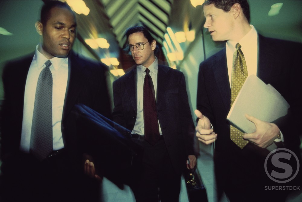 Stock Photo: 1189-243A Three businessmen walking in a corridor