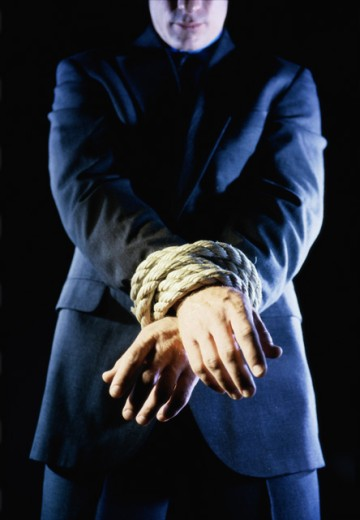 Businessman's hands tied together with a rope : Stock Photo