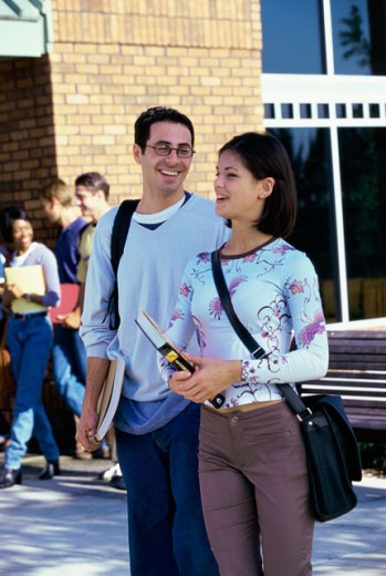 Young man and a young woman walking on a college campus : Stock Photo