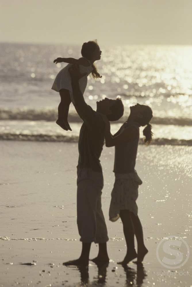 Silhouette of a young couple on the beach with their daughter : Stock Photo