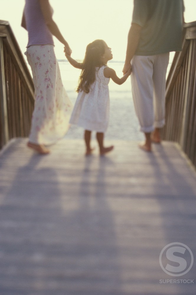 Stock Photo: 1189-2815B Rear view of a girl with her parents walking on a boardwalk