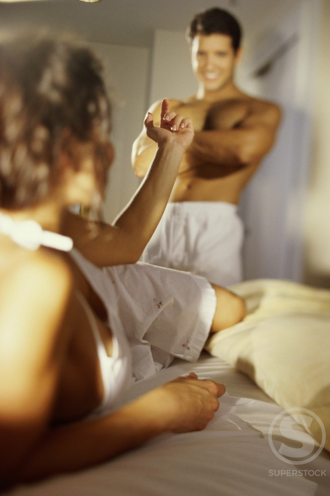 Stock Photo: 1189-2828B Young woman lying in bed and gesturing to a young man