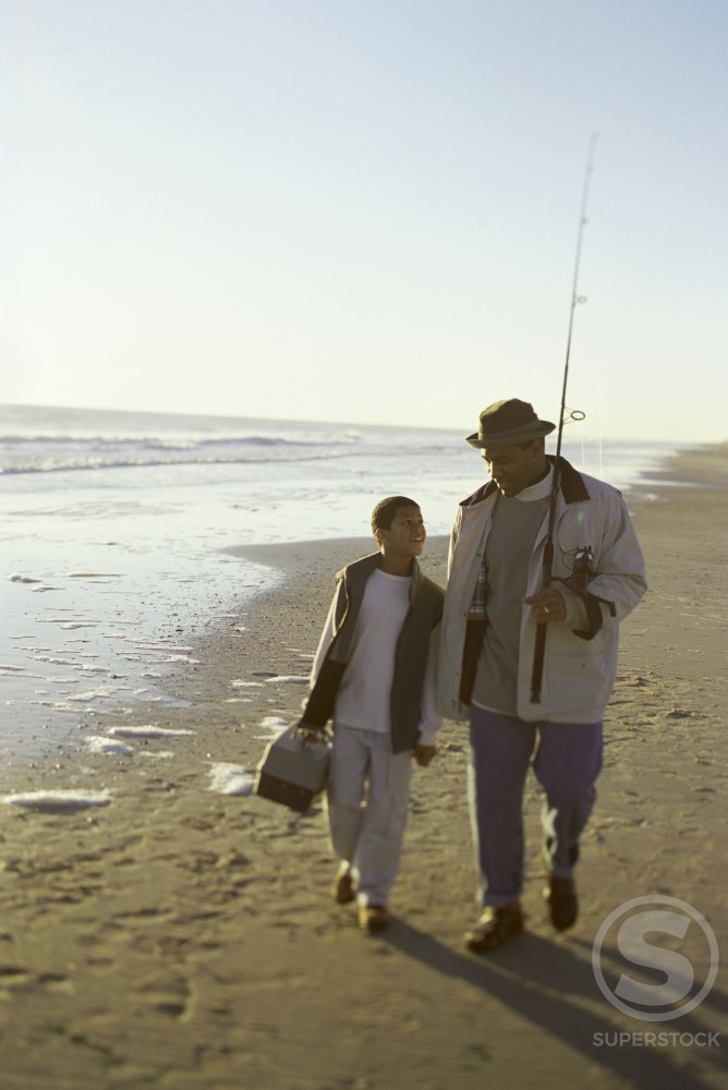 Father and his son walking on the beach with fishing gear : Stock Photo