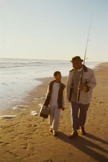 Stock Photo: 1189-2968B Mid adult man walking with his son and holding a fishing pole