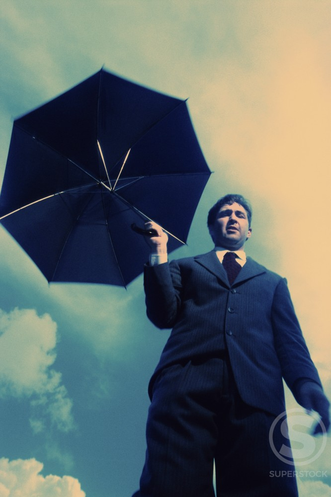 Low angle view of a businessman holding an umbrella : Stock Photo