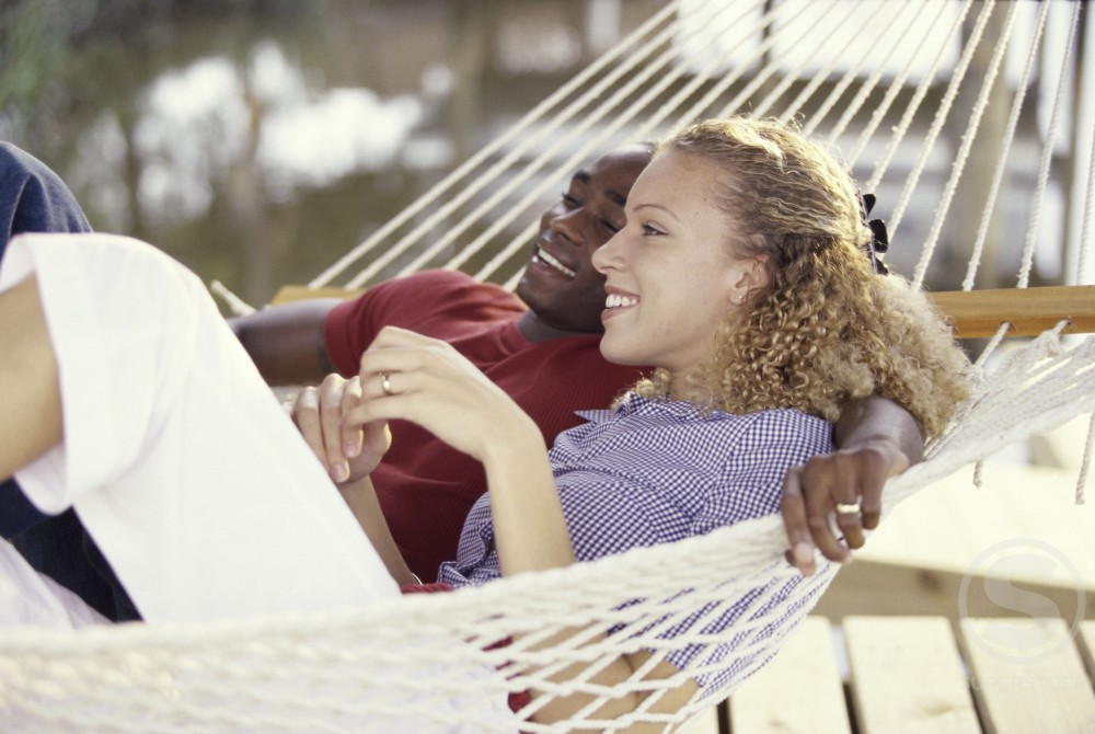 Stock Photo: 1189-3705A Young couple lying in a hammock