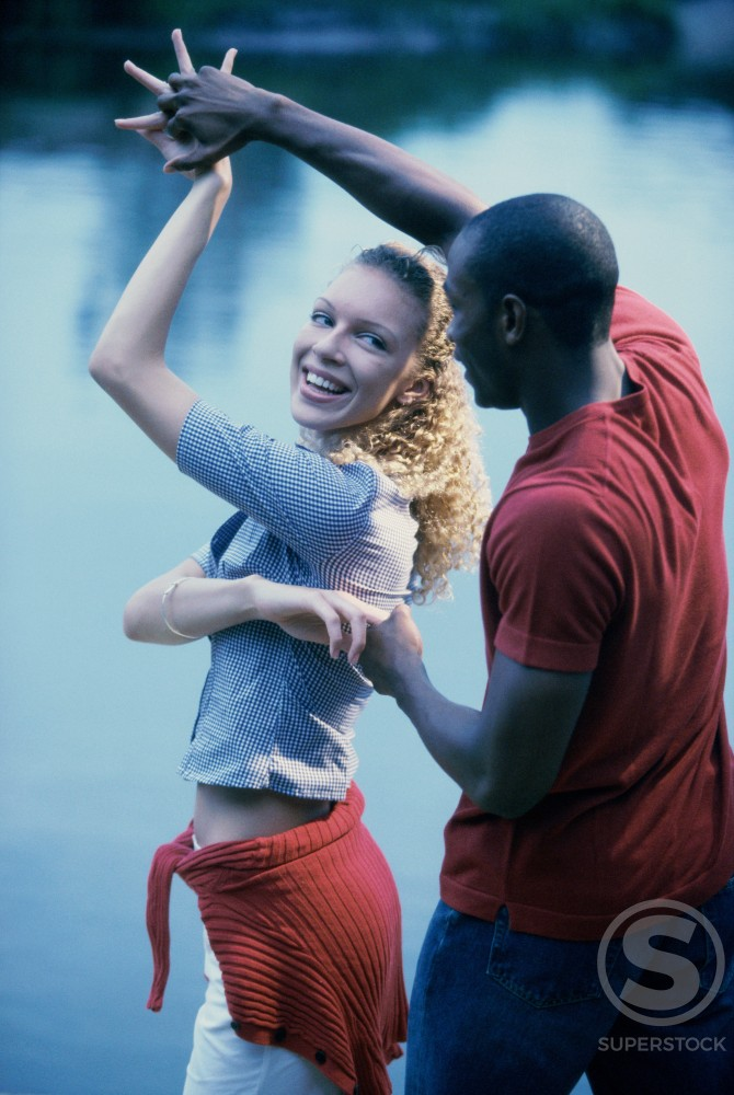 Stock Photo: 1189-3708F Young couple dancing by a lake