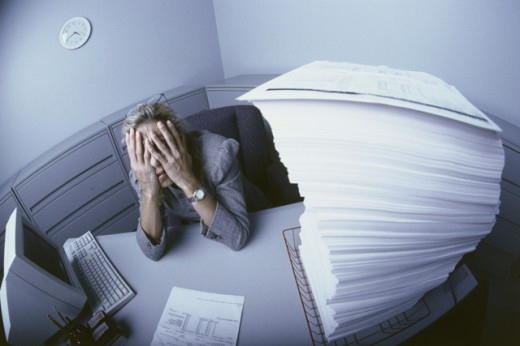 Stock Photo: 1189-3798 Businesswoman sitting at a desk with her hands covering her face