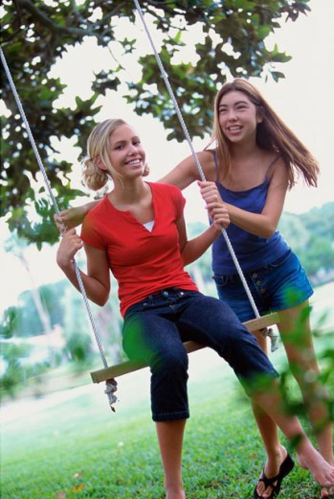 Two teenage girls swinging on a swing : Stock Photo