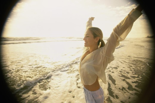 Young woman with her arms raised on the beach : Stock Photo