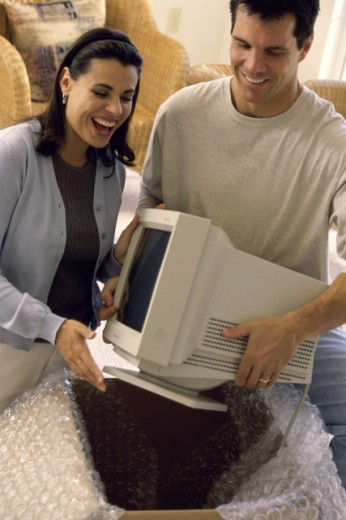 Stock Photo: 1189-393 Young couple unpacking a computer monitor