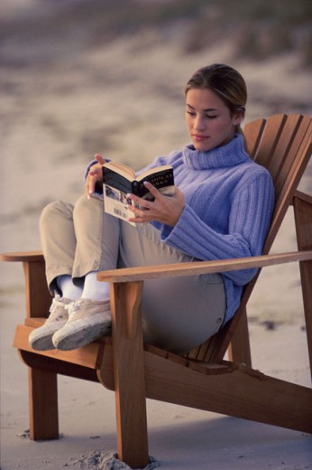 Stock Photo: 1189-3940B Young woman reading a book on the beach