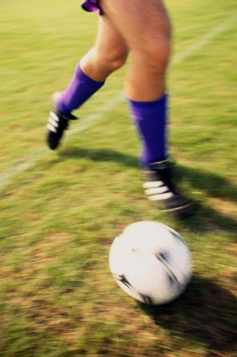 Stock Photo: 1189-4098 Low section view of a soccer player playing with a soccer ball