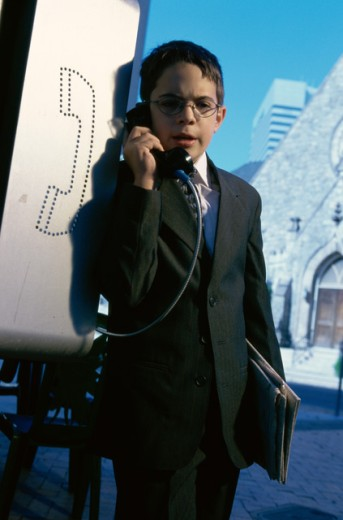 Portrait of a boy wearing a business suit talking on a pay phone : Stock Photo