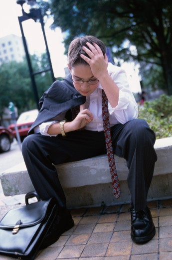 Stock Photo: 1189-4133B Boy wearing a business suit resting