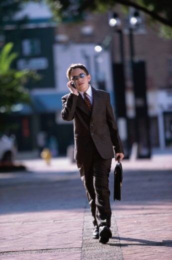 Stock Photo: 1189-4137A Boy wearing a business suit talking on a mobile phone