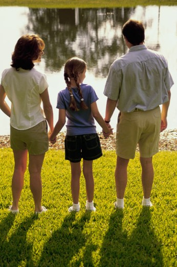 Stock Photo: 1189-578B Rear view of a mid adult couple with their daughter standing in front of a lake