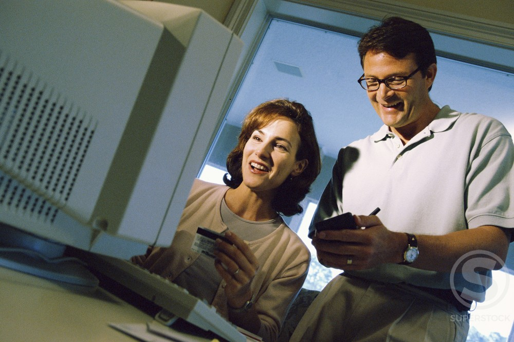 Stock Photo: 1189-597B Mid adult couple using a computer
