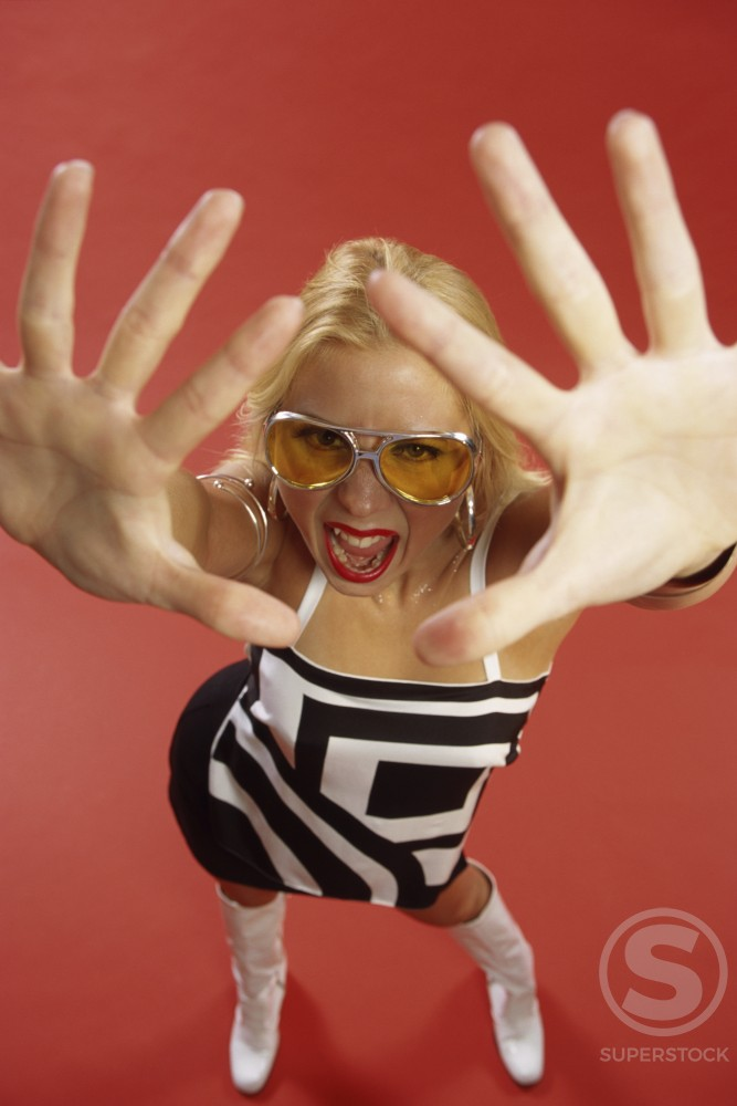 Portrait of a young woman with her hands in front of her face : Stock Photo