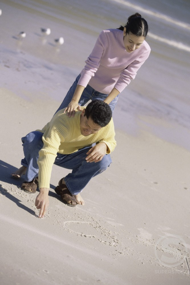 Young man writing in the sand with a young woman leaning on him : Stock Photo