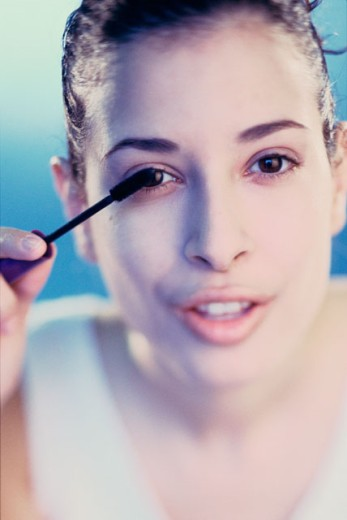 Stock Photo: 1189R-3583C Portrait of a young woman applying mascara