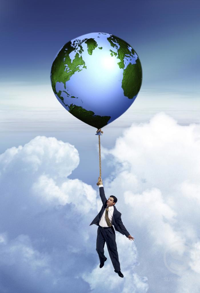 Businessman holding onto a floating globe : Stock Photo