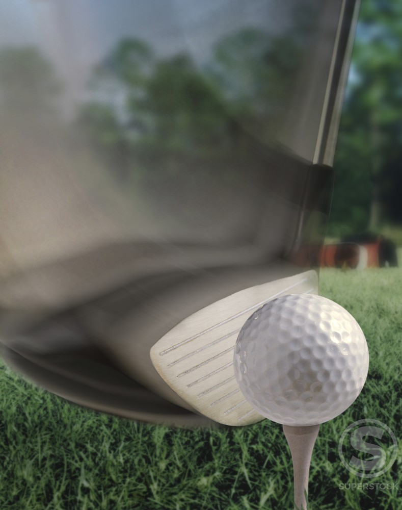 Close-up of a golf club hitting a golf ball on a tee : Stock Photo