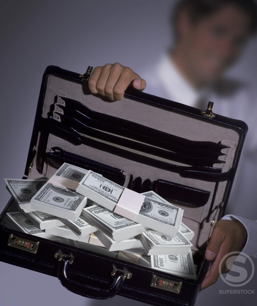 Stock Photo: 1199-140 Businessman holding an open briefcase with American dollar bills