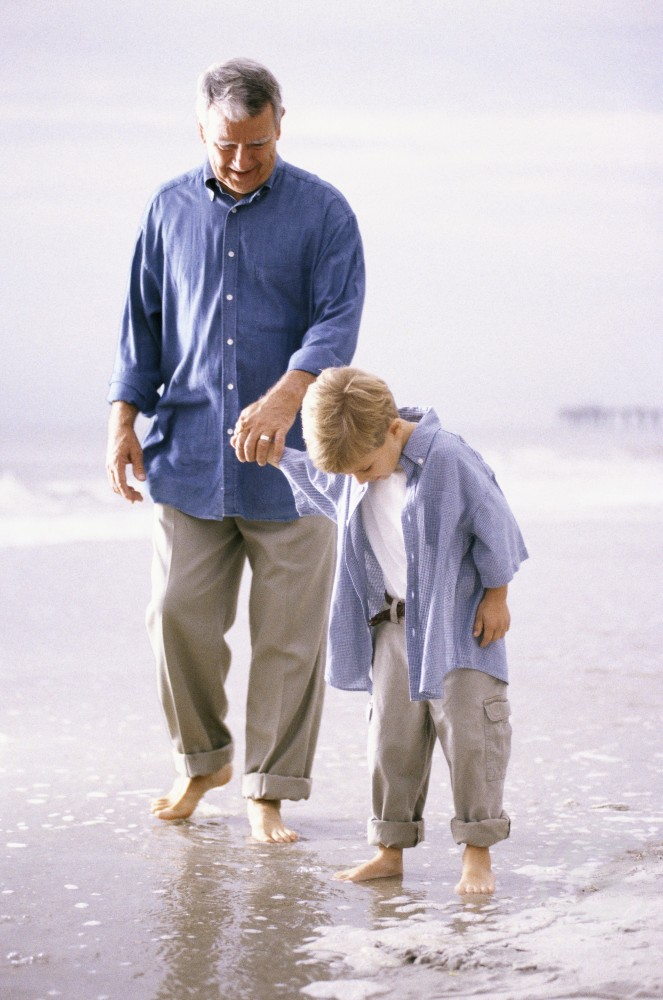 Stock Photo: 1201-110A Grandfather and his grandson walking on the beach