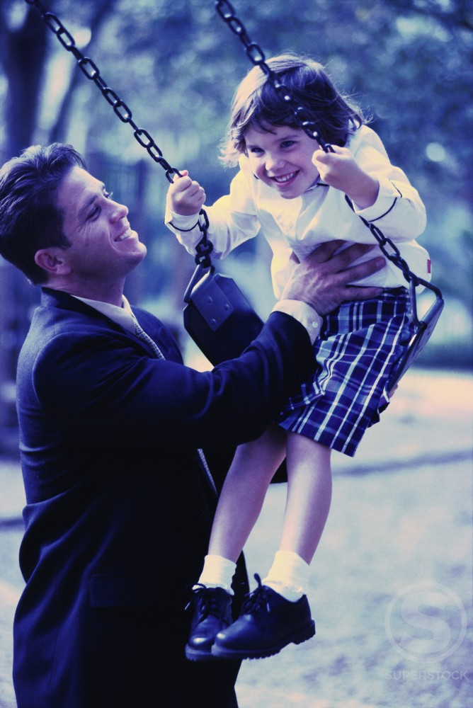 Stock Photo: 1202-104 Father pushing his daughter on a swing