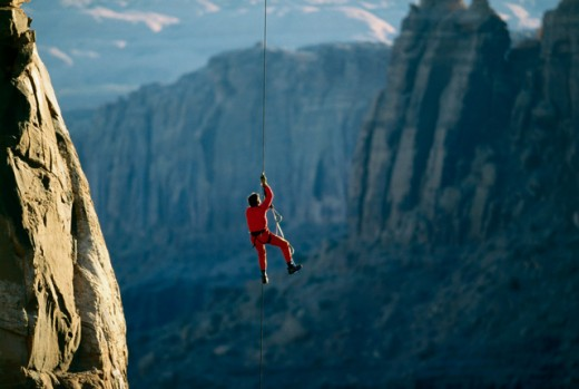 Stock Photo: 1217-207 Rear view of a man rappelling down a rock