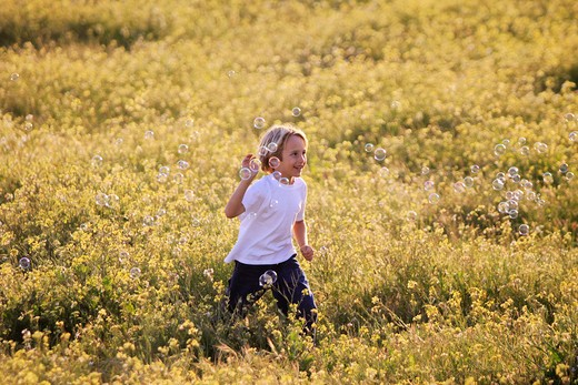 Stock Photo: 1217-499B Boy playing with bubbles in a field