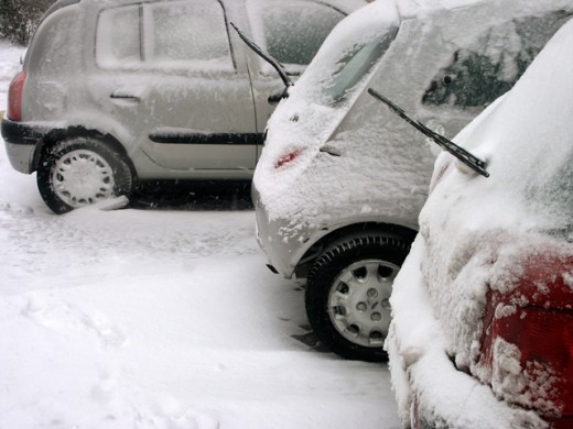 Three cars covered with snow in a parking lot : Stock Photo