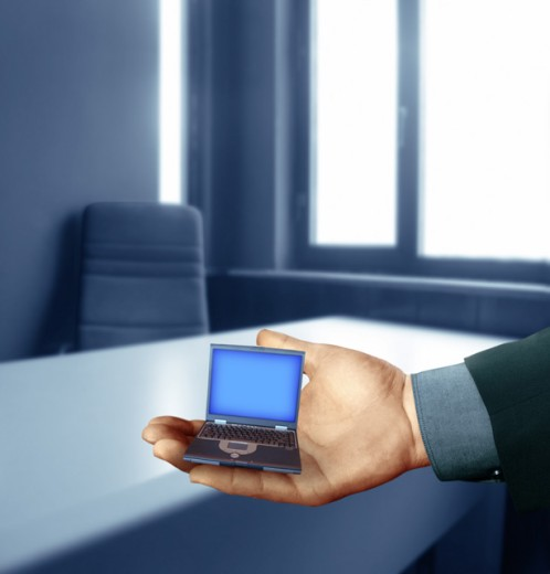 Person's hand holding a miniature laptop : Stock Photo