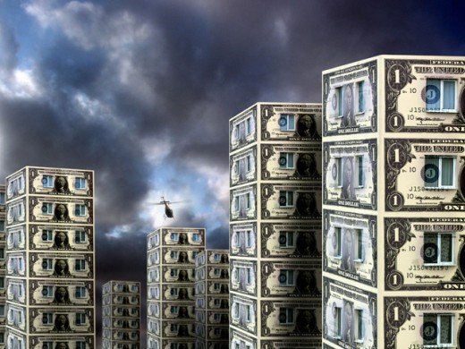 Buildings made of paper money with a helicopter flying above : Stock Photo