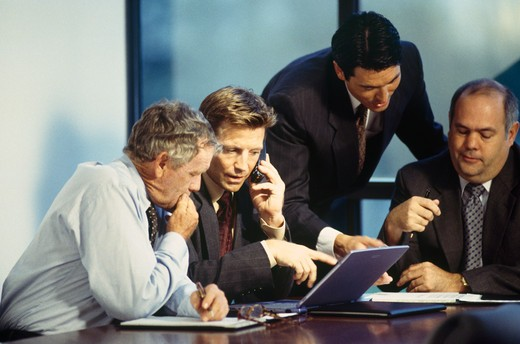 Four businessmen talking in a meeting : Stock Photo