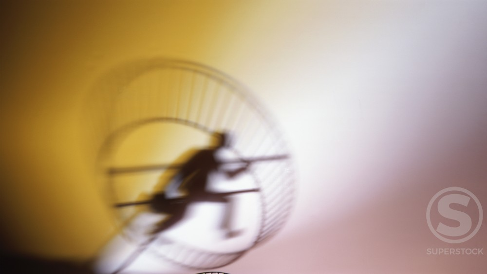 Stock Photo: 1236-156 Silhouette of a businessman running in an exercise wheel